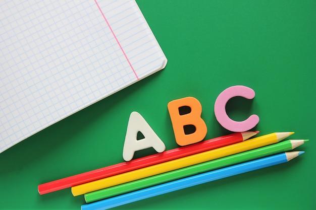 Abc-les premières lettres de l'alphabet anglais. cahier d'école et crayons de couleur Photo Premium