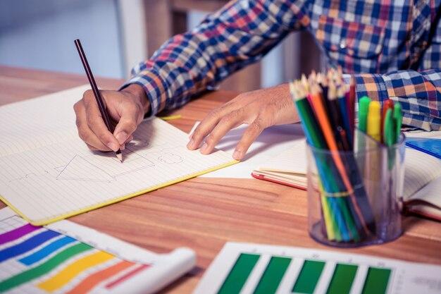 Abdomen de concepteur dessinant un livre au bureau dans un bureau créatif Photo Premium