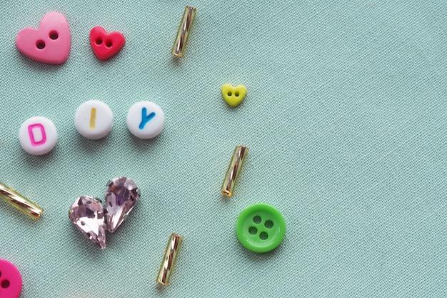 Abréviation de perles de plastique bricolage parmi les boutons, les cristaux, les perles de verre sur un fond de tissu bleu. faites-le vous-même Photo Premium