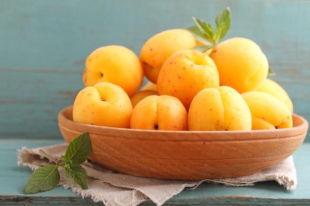 Abricots dans une assiette en bois avec des feuilles de menthe Photo Premium
