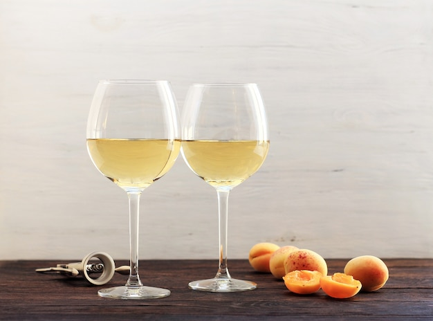 Abricots et deux verres de vin blanc Photo Premium