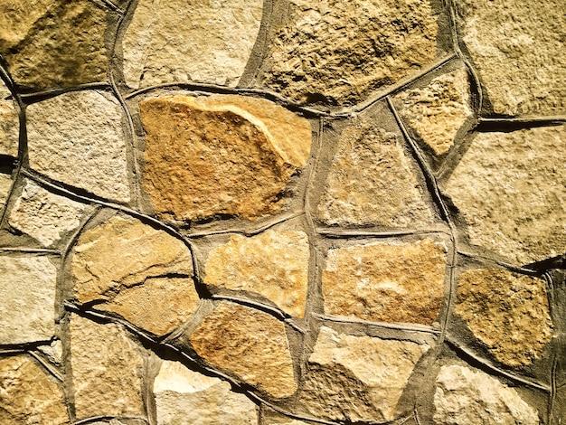 Abstrait Fond Texturé Avec Des Pierres Naturelles En Mosaïque De Différentes Formes Sur Le Mur. Photo Premium