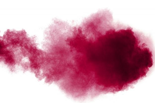 Abstraite poussière rouge éclaboussée sur fond blanc. explosion de poudre rouge. figer le mouvement des particules rouges éclaboussant. Photo Premium