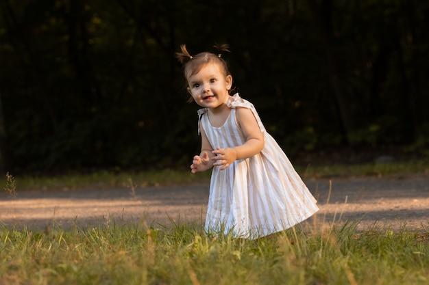 Aby Girl S'amuse Dans Le Parc, Courir Pieds Nus Sur L'herbe Verte. Photo Premium