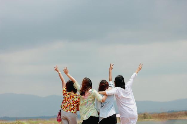 Accent doux et flou avec des amis de la femme heureuse s'amusant et exprimant leurs émotions regardant la montagne Photo Premium