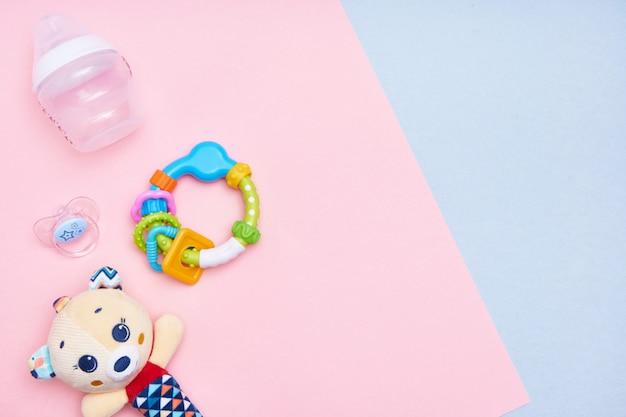 Accessoires Bébé Sur Fond Rose Et Bleu. Mise à Plat. Vue De Dessus Espace Copie. Photo Premium