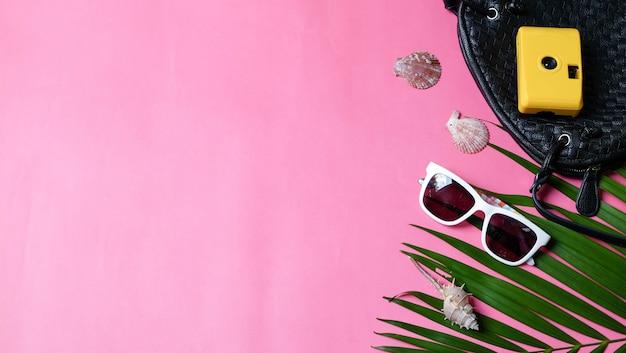 Accessoires caméra de voyage sac à bandoulière noir et lunettes de soleil feuille de palmier. vue de dessus concept été fond. Photo Premium