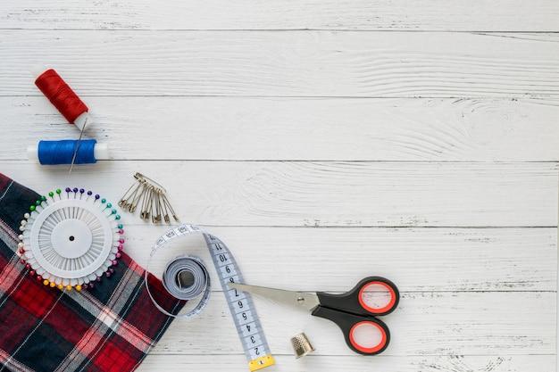 Accessoires de couture. tissu à carreaux sur un fond en bois blanc. Photo Premium