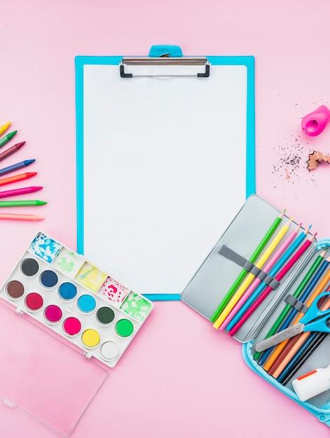 Accessoires de dessin colorés et presse-papiers sur fond rose Photo gratuit
