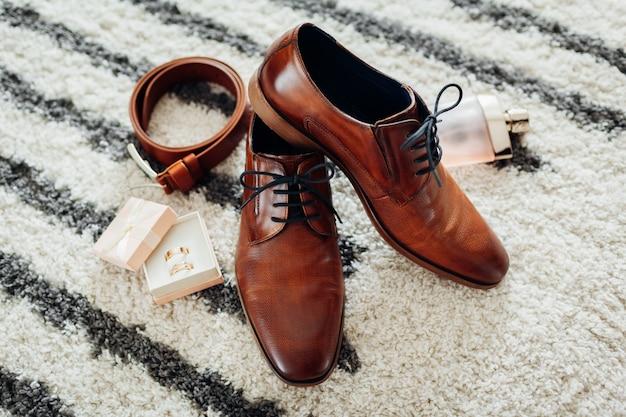 Accessoires du jour du mariage du marié. chaussures en cuir marron, ceinture, parfum, bagues dorées. mode masculine Photo Premium