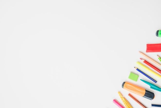 Accessoires d'école colorée sur le coin du fond blanc Photo gratuit