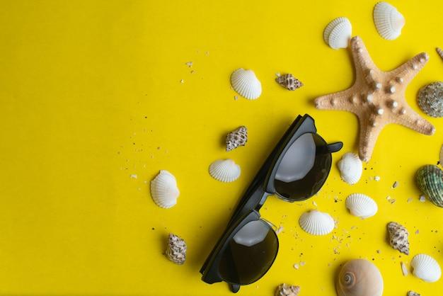 Accessoires d'été, coquilles et lunettes de soleil sur une surface jaune. Photo Premium