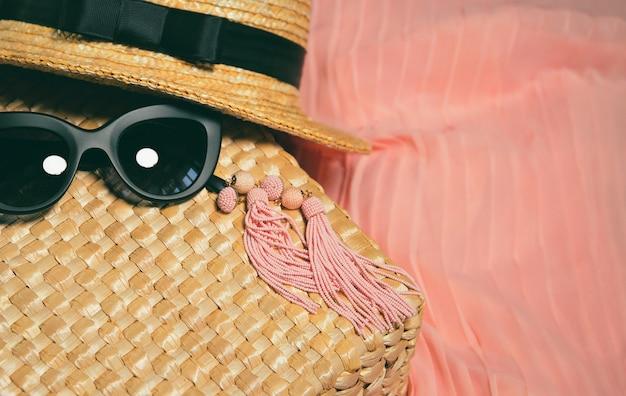 Accessoires femme. fragment d'un sac de paille, boucles d'oreilles, chapeau de paille, lunettes de soleil à la mode noires Photo Premium