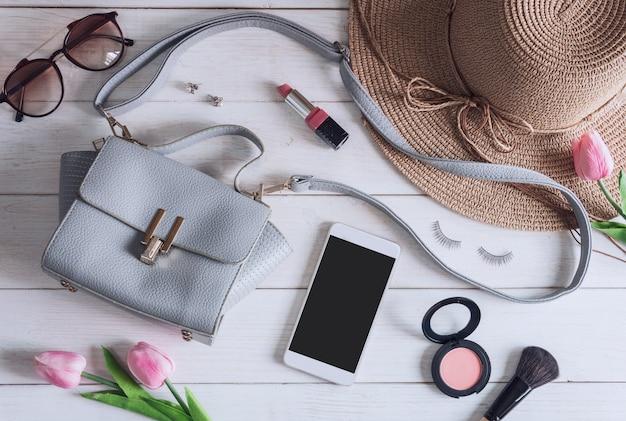 Accessoires femme avec maquillage, cosmétiques, pinceau et téléphone intelligent Photo Premium