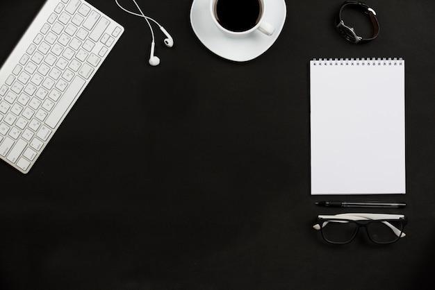 Accessoires personnels; tasse à café; écouteur; lunettes et clavier sur fond noir Photo gratuit