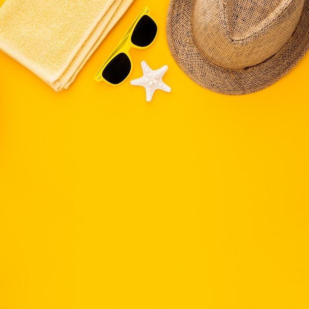 Accessoires de plage sur le fond jaune. étoile de mer, lunettes de soleil, serviette et chapeau à rayures. Photo gratuit