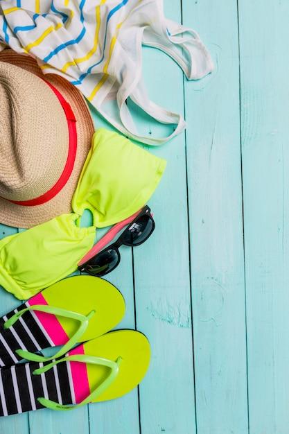Accessoires de plage avec maillot de bain jaune, lunettes de soleil et tongs Photo Premium