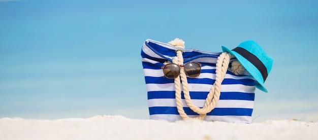 Accessoires de plage - sac bleu, chapeau de paille, lunettes de soleil sur la plage blanche Photo Premium