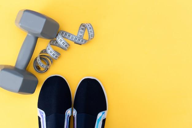 Accessoires De Remise En Forme Sur Fond Jaune. Sneakers, Bouteille D'eau, écouteurs Et Haltères. Photo Premium