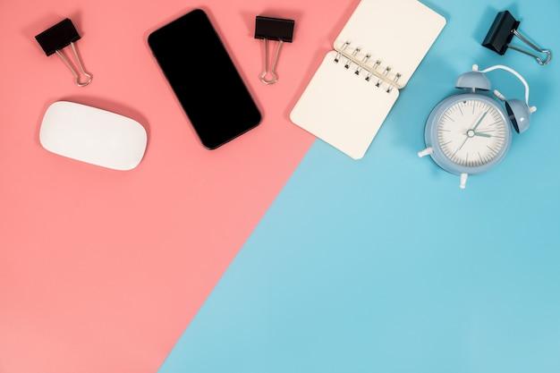 Accessoires de smartphone et de bureau sur un fond coloré avec espace de copie. lay plat. Photo Premium
