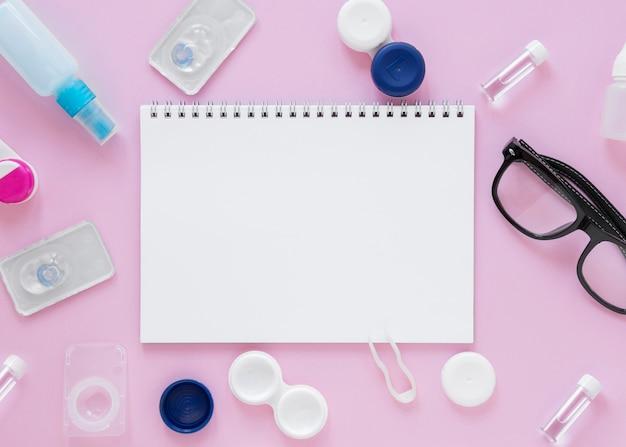 Accessoires de soins oculaires sur fond rose avec maquette de l'ordinateur portable Photo gratuit