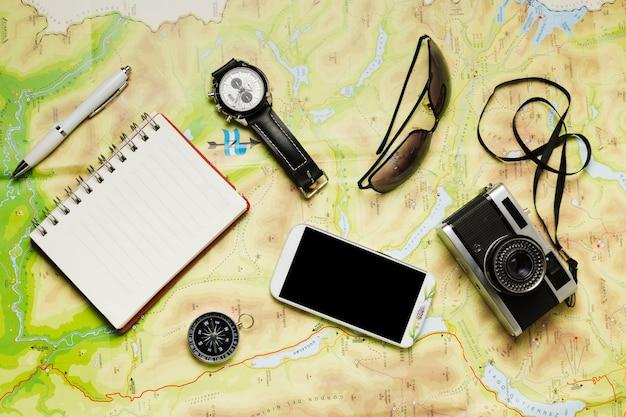 Accessoires de voyage plats laïcs sur fond de carte Photo gratuit