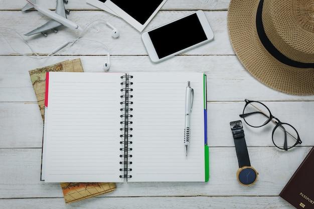 Les accessoires de vue de dessus pour le concept de voyage. l'espace gratuit pour écrire avec stylo sur la table blanche backgroun.items est la carte, la montre, les lunettes, le passeport, le chapeau, le téléphone mobile, l'avion, le téléphone des yeux, la photo. Photo gratuit
