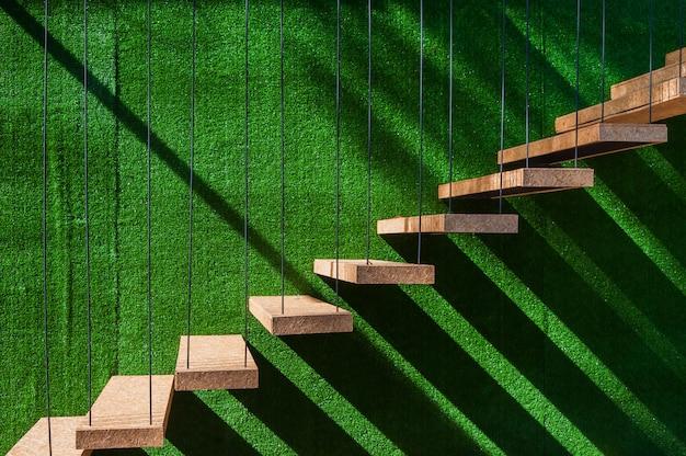 Accrocher des escaliers en bois sur le mur de gazon artificiel Photo Premium