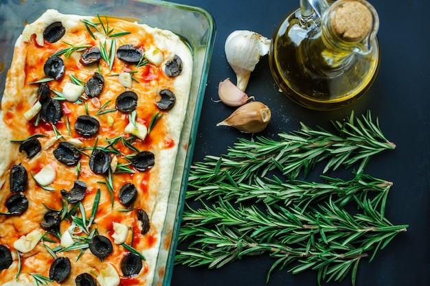 Accueil focaccia aux olives et au romarin sur une table noire Photo Premium