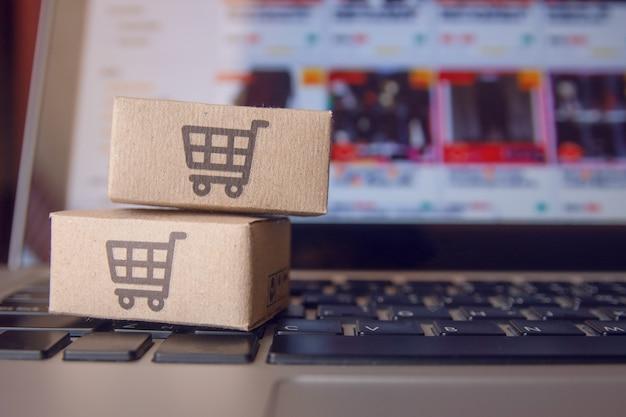 Achats en ligne: cartons de papier ou colis portant le logo d'un panier d'achat sur un clavier d'ordinateur portable. service d'achat sur le web en ligne et offre la livraison à domicile. Photo Premium