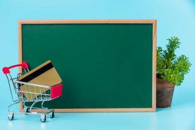 Les achats en ligne, un double panier placé sur un tableau vert sur un bleu. Photo gratuit