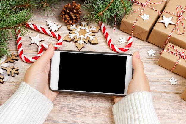 Achats en ligne de noël. femme acheteur rend la commande à l'écran du smartphone avec fond. femme achète des cadeaux pour la veille de noël, reste à la maison près de décorée. soldes de vacances d'hiver Photo Premium