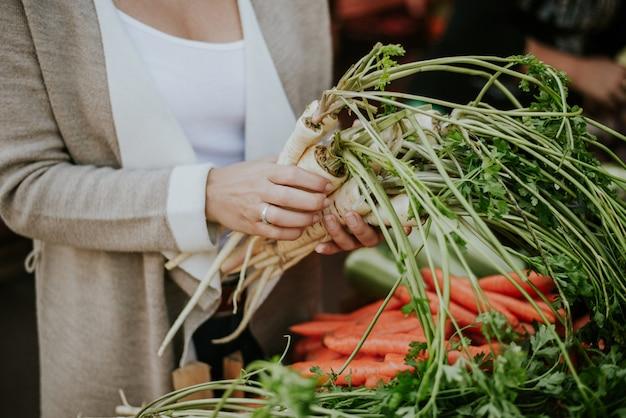 Acheter des légumes au marché. légumes dans les mains agrandi. Photo Premium