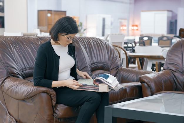 Acheteur femme adulte regardant un livre avec des tissus d'ameublement Photo Premium
