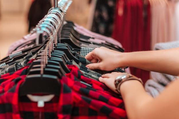 Une acheteuse choisit un t-shirt dans une boutique. Photo Premium