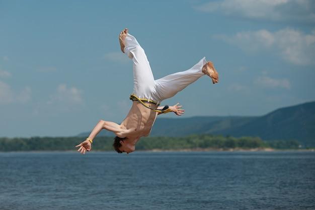 Acrobat effectue un tour acrobatique, un saut périlleux sur la plage. Photo Premium