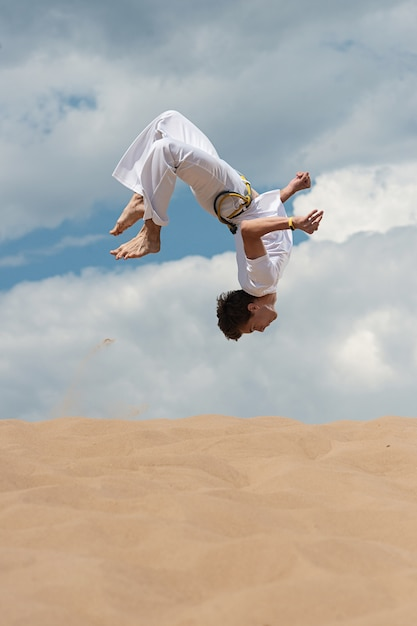 Acrobat effectue un tour acrobatique, un saut périlleux sur la plage Photo Premium
