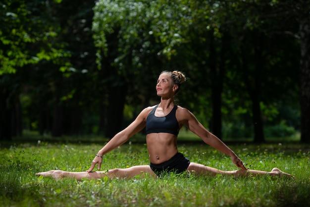 Acrobate fille exécute élément acrobatique sur l'herbe dans le parc Photo Premium