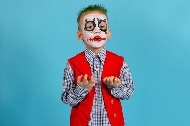 L'acteur Fait Peur Avec Ses Doigts. Joyeux Halloween. Garçon En Costume Sur Mur Bleu Avec Espace Libre. Photo Premium