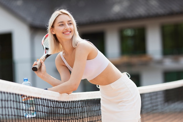 Actif jeune fille se reposant sur le filet de tennis Photo gratuit