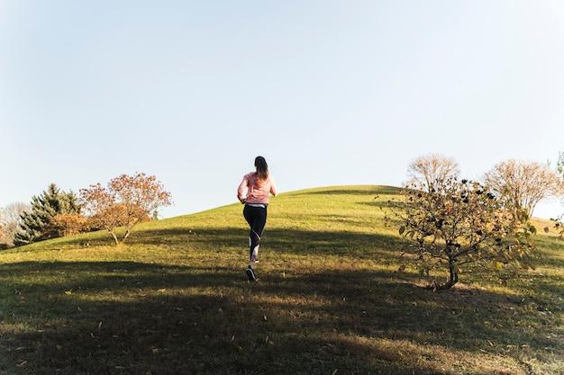 Active jeune femme qui court dans le parc Photo gratuit