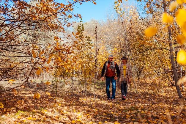 Activités D'automne. Senior Couple Marchant Dans Le Parc En Automne. Homme D'âge Moyen Et Femme étreignant Et Se Détendre En Plein Air Photo Premium