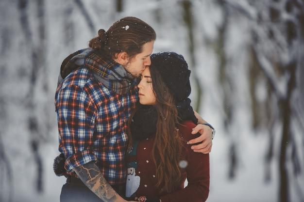 Activités Saisonnières En Plein Air Couple Marchant Dans La Forêt D'hiver Enneigé Photo Premium