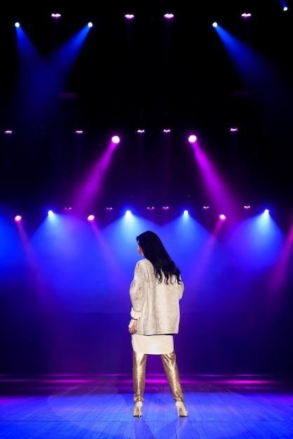 Actrice Sur Scène Dans Des Faisceaux Lumineux Colorés. Photo Premium