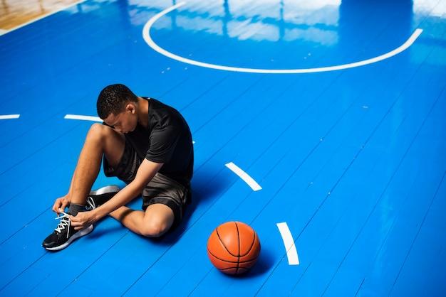 Un adolescent afro-américain attachant ses lacets sur un terrain de basket Photo gratuit