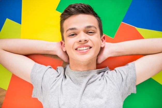 Adolescent allongé sur le sol coloré. Photo Premium