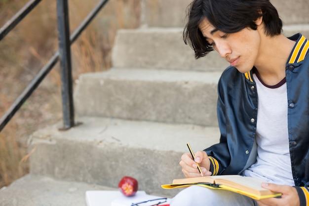 Adolescent asiatique assis avec livre dans les escaliers Photo gratuit