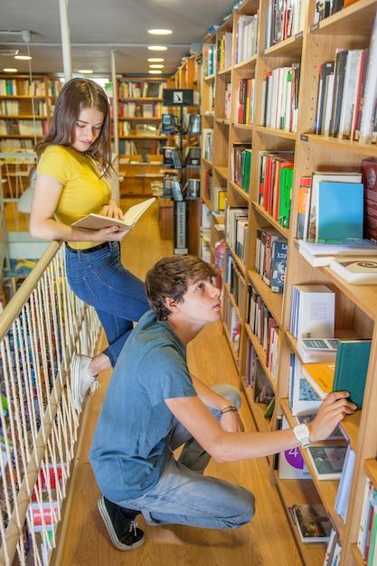 Adolescent assis sur les hanches et en choisissant un livre près de la petite amie Photo gratuit