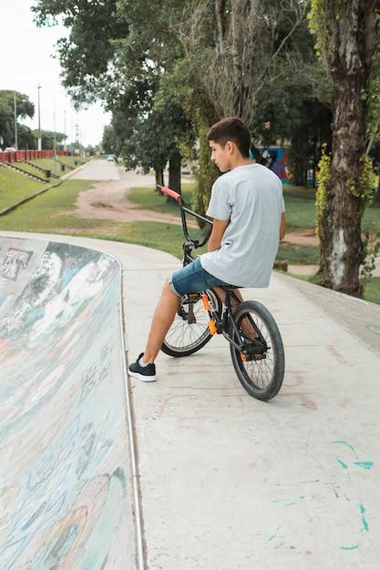 Adolescent assis à vélo sur le skate park en béton Photo gratuit