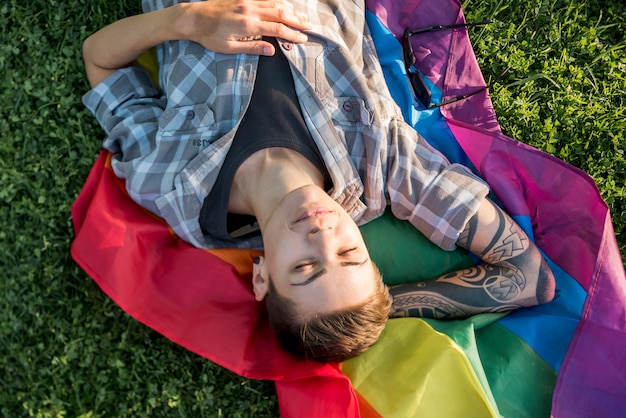 Adolescent aux cheveux courts sur drapeau lgbt Photo gratuit
